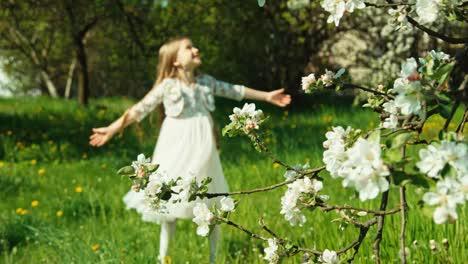 Niña-7-8-Años-Girando-En-El-Vestido-Blanco-En-El-Parque-Cerca-Del-árbol-Floreciente