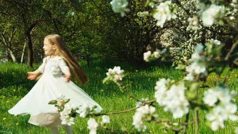 Girl-7-8-Years-Spinning-In-The-White-Dress-In-The-Park-Near-Blooming-Tree