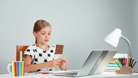 Girl-7-8-Years-Using-Laptop-And-Eating-Chocolate-Child-Holding-A-Chocolate
