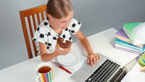 Girl-7-8-Years-Using-Laptop-And-Eating-Donut-Top-View