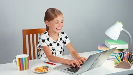 Girl-7-8-Years-Using-Laptop-And-Eating-Marmalade-Candy-Child-Doing-Homework