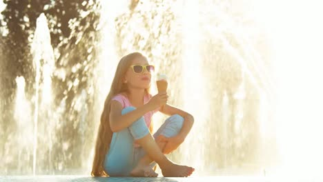 Girl-8-Years-Old-Eating-Icecream-Near-Fountain-At-Sunny-And-Hot-Day-Smiling