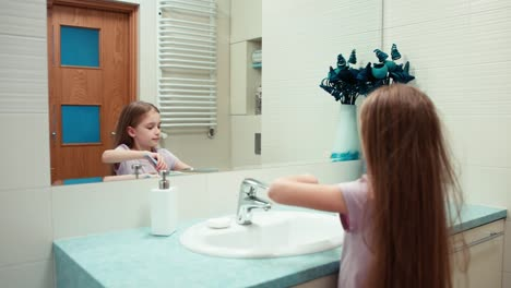 Girl-Brushing-Her-Teeth-In-The-Bathroom-Standing-In-Front-Of-A-Mirror
