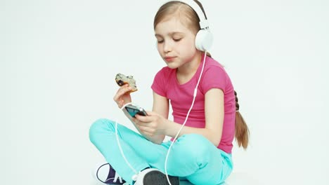Girl-Child-7-8-Years-Eating-Muffin-And-Using-Mobile-Phone-And-Listening-Music