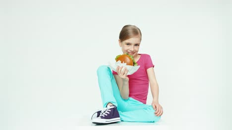 Girl-Child-7-8-Years-Old-Holding-Burger-And-Laughing-And-Sitting-On-The-White