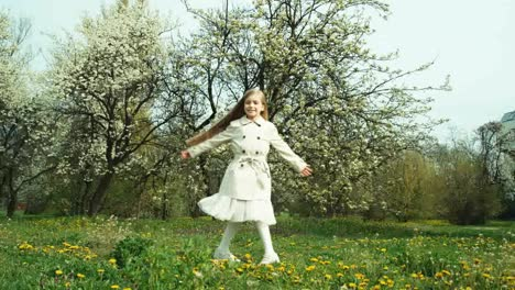 Girl-Child-7-8-Years-Old-In-Coat-Spinning-Against-The-Backdrop-Of-Flowering