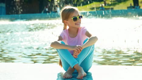 Girl-Child-7-8-Years-Relaxing-Near-Fountain-At-Sunny-Day