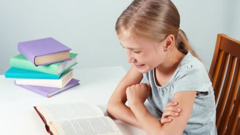 Girl-Child-Student-Reading-Book-And-Laughing-Schoolgirl-Sitting-In-The-Table