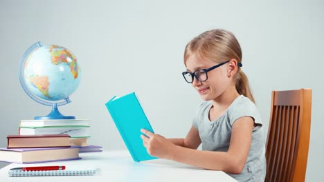 Girl-Foureyes-Reading-Her-Textbook-And-Smiling-At-Camera