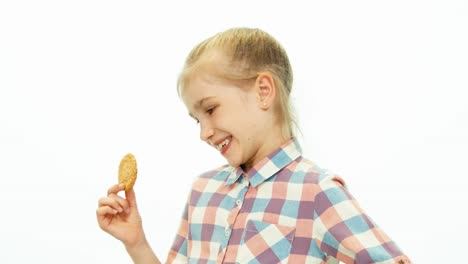 Girl-Holding-A-Cookie-And-Smiling-At-Camera-On-The-White-Background