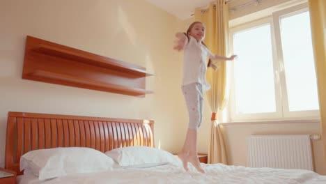 Niña-Saltando-En-La-Cama-En-La-Habitación-Soleada-Slowmotion