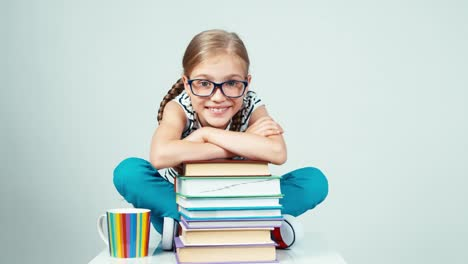 Girl-Leaning-On-Books-And-Smiling-At-Camera-And-Napping