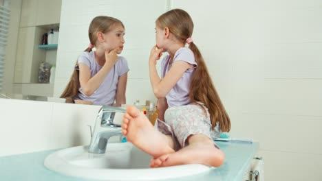 Mädchen-Schaut-Auf-Ihre-Zähne-Die-Neben-Dem-Spiegel-Im-Badezimmer-Sitzen-In