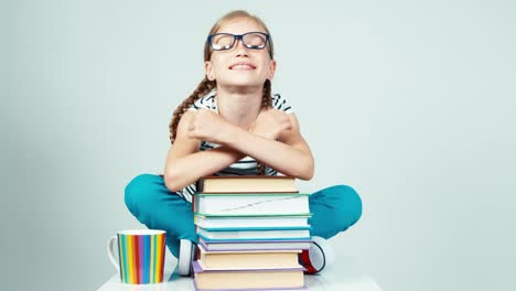 Girl-Napping-On-Books-And-Smiling-At-Camera-With-Teeth
