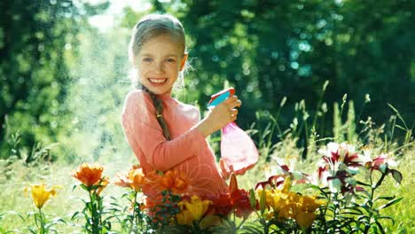 Girl-Playing-With-Sprinkler-Near-Flowers-In-The-Garden-And-Smiling