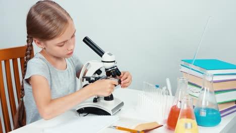 Niña-Pone-El-Portaobjetos-Bajo-El-Microscopio-Y-Sonriendo-A-La-Cámara-Con-Dientes