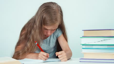 Girl-Something-Writing-In-Her-Notebook-And-Looking-At-Camera-Isolated-On-White