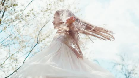 Girl-Spinning-In-A-Dress-On-A-Background-Of-Blooming-Trees-Slow-Motion