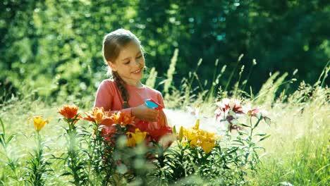Girl-Sprinkler-Flowers-In-The-Garden-And-Smiling-At-Camera