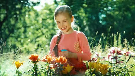 Girl-Sprinkling-Flowers-In-The-Garden-And-Smiling-At-Camera