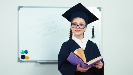 Graduate-In-The-Mantle-Hugging-Book-Close-Up-Portrait-Little-Student-Girl