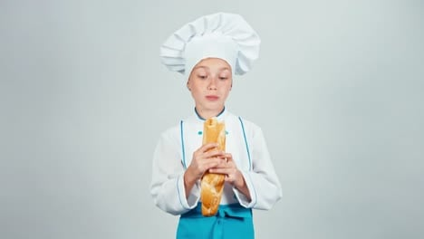 Happy-Baker-Girl-7-8-Years-Child-Eating-Baguette-Bread-And-Smiling-At-Camera