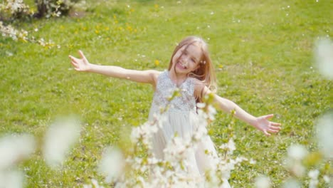 Happy-Blonde-Girl-7-8-Years-Old-Whirling-In-A-White-Dress-On-The-Grass