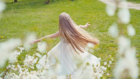 Happy-Blonde-Girl-7-8-Years-Old-Whirling-In-A-White-Dress-On-The-Grass-Slow