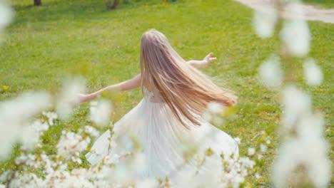 Feliz-Chica-Rubia-De-7-8-Años-Girando-En-Un-Vestido-Blanco-Sobre-La-Hierba-Lenta