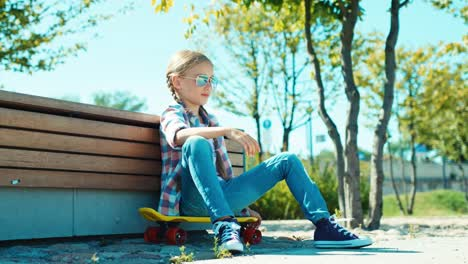 Happy-Girl-In-Sunglasses-Sitting-On-The-Skateboard-Near-Bench-In-The-Park-And