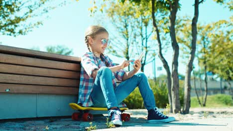 Girl-In-Sunglasses-Using-Her-Smartphone-Sitting-On-The-Skateboard-Near-Bench