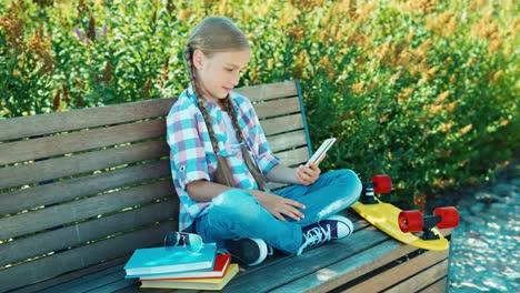 Niña-Feliz-Escribiendo-Sms-En-Su-Teléfono-Inteligente-Sentado-En-El-Banco-En-El-Parque