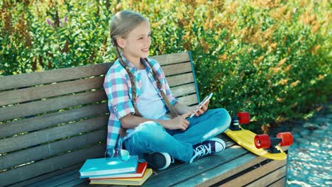 Happy-Girl-Using-Smartphone-Sitting-On-The-Bench-In-The-Park-And-Smiling