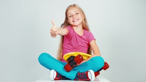 Happy-School-Girl-Holding-Penny-Skateboard-And-Sitting-On-Floor-Thumb-Up-Ok