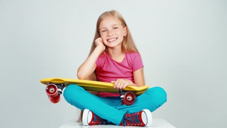 Happy-School-Girl-Holds-Penny-Skateboard-And-Sitting-On-The-Floor