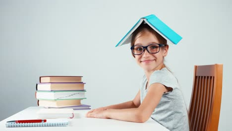 Happy-Schoolgirl-Child-7-8-Years-Old-Holding-Book-On-Her-Head-And-Smiling