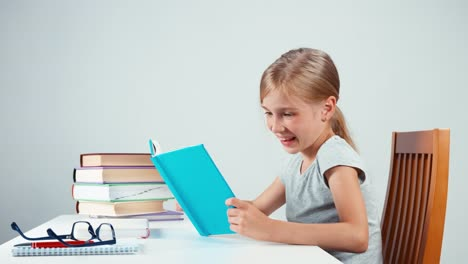 Feliz-Colegiala-De-7-8-Años-Sosteniendo-Su-Libro-Y-Leyendo-Con-Una-Sonrisa