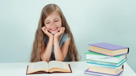 Happy-Schoolgirl-7-8-Years-Old-Reading-Book-On-The-Table-And-Looking-At-Camera