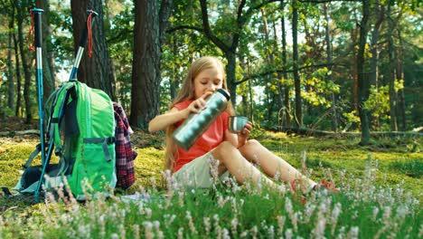 Niña-Excursionista-8-9-Años-Vierte-Té-De-Un-Termo-Sentado-En-El-Césped-Y-Beber-Té