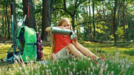 Niña-Excursionista-8-9-Años-Vierte-Té-De-Un-Termo-Sentado-En-El-Césped-En-El-Bosque