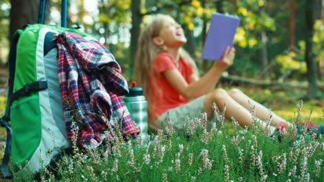 Niña-Excursionista-8-9-Años-Leyendo-El-Libro-En-El-Bosque-Y-Riendo