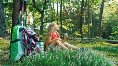 Niña-Excursionista-8-9-Años-Relajándose-Y-Bebiendo-Té-En-El-Bosque-Y-Sonriendo