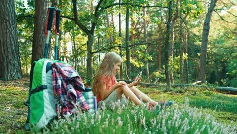 Niña-Excursionista-8-9-Años-Usando-El-Teléfono-Celular-Y-Sentado-En-La-Hierba-En-El-Bosque