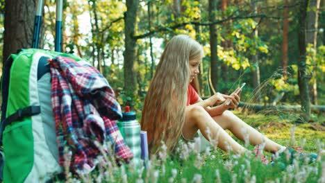 Niña-Excursionista-8-9-Años-Con-Teléfono-Inteligente-Y-Riendo-Sentado-En-La-Hierba