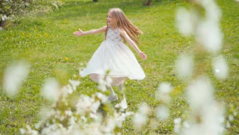 Laughing-Blonde-Girl-Whirling-In-A-White-Dress-On-The-Grass-In-The-Park-Slow