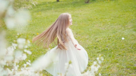 Laughing-Blonde-Girl-Whirling-In-A-White-Dress-On-The-Grass-Slow-Motion