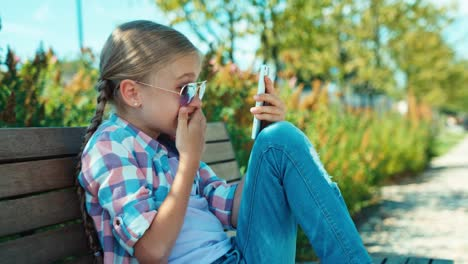 Laughing-School-Girl-7-8-Years-Using-Smartphone-And-Sitting-On-The-Bench