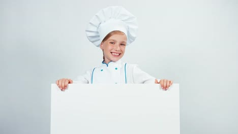 Little-Cute-Chef-Cook-Pointing-Finger-To-Whiteboard-And-Smiling-With-Teeth