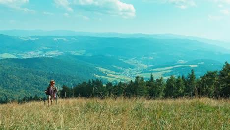 Kleines-Wanderermädchen-Das-Den-Hügel-Hinauf-Auf-Berghintergrund-Bei-Der-Kamera-Geht