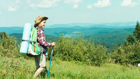 Little-Hiker-Girl-With-Travel-Backpack-Going-Down-Hill-On-Mountains-Background